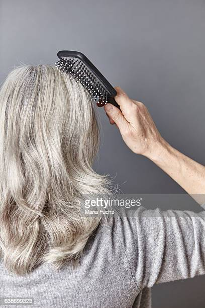 Rear view of woman brushing long gray hair