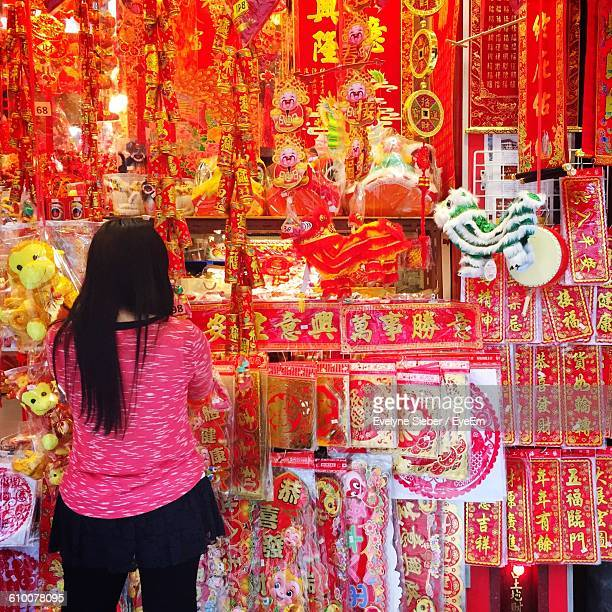Rear View Of Woman Buying Decorations At Street Market