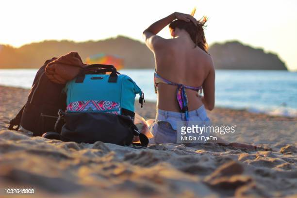 Rear View Of Woman By Bags Sitting On Sandy Beach