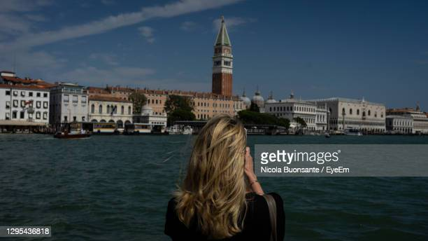 rear view of woman by buildings against sky in city - monza stock pictures, royalty-free photos & images