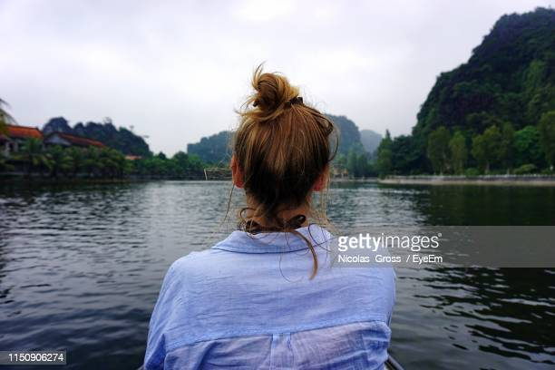 rear view of woman by lake against sky - up do stock pictures, royalty-free photos & images