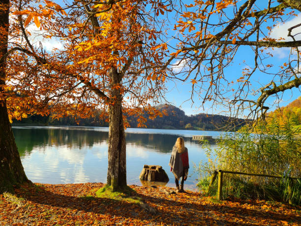 Rear View Of Woman By Lake During Autumn