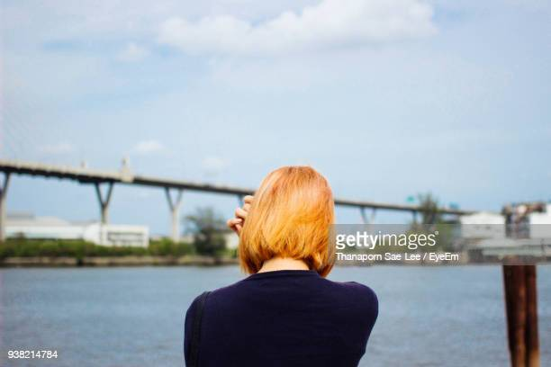 Rear View Of Woman By River Against Sky