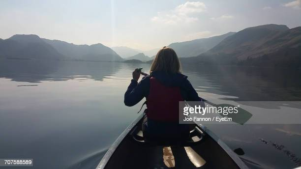 rear view of woman canoeing in lake by mountains against sky - derwent water - fotografias e filmes do acervo