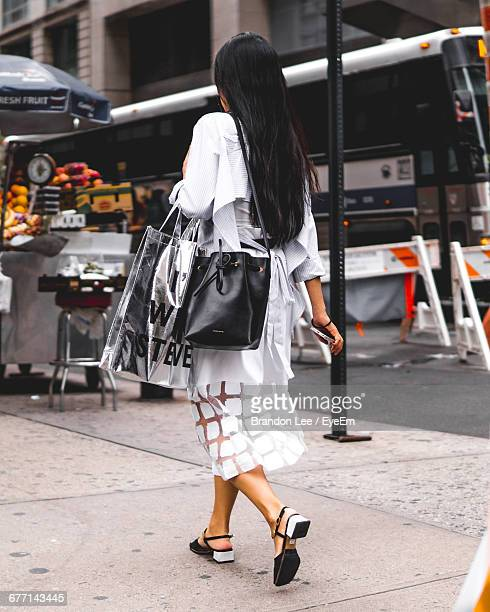 Rear View Of Woman Carrying Bags And Walking On Footpath