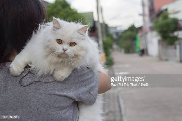 Rear View Of Woman Carrying Cat On Shoulder At Footpath