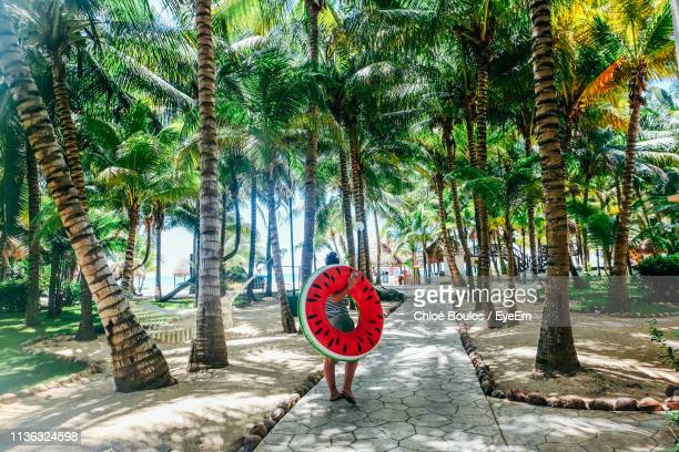 rear view of woman carrying inflatable ring while walking on footpath - playa del carmen stock pictures, royalty-free photos & images