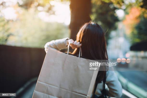 rear view of woman carrying shopping bag over shoulder walking on city street - shopping bag stock pictures, royalty-free photos & images