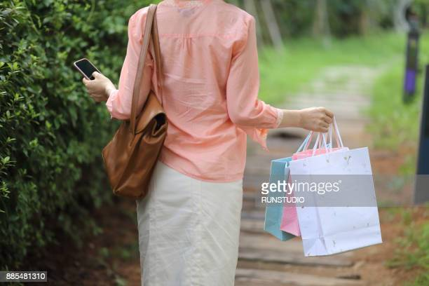 Rear view of woman carrying shopping bags outdoors