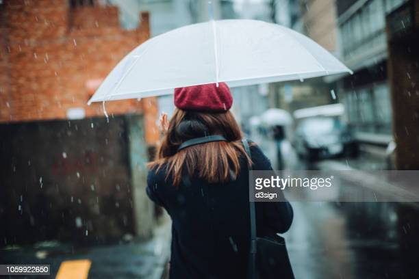 rear view of woman carrying umbrella walking in the snow in city - umbrella stock pictures, royalty-free photos & images
