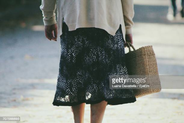 Rear View Of Woman Carrying Wicker Shopping Bag On Footpath