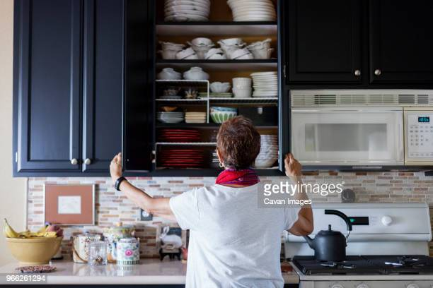 rear view of woman checking cabinet in kitchen - arrangement stock pictures, royalty-free photos & images