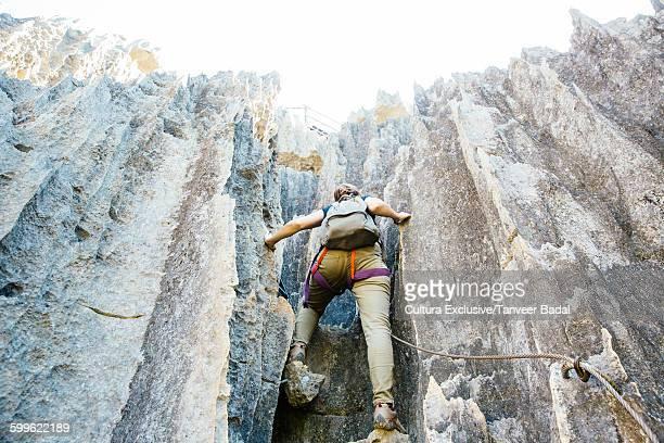 Rear view of woman climbing Tsingy de Bemaraha National Park, Madagascar, Africa