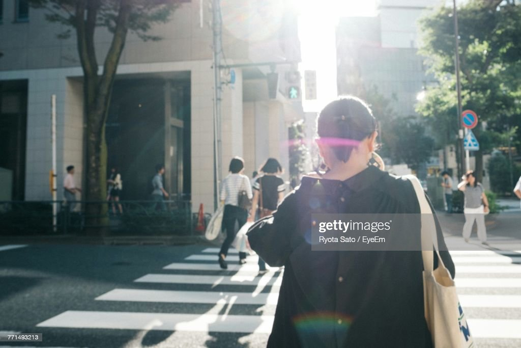 Rear View Of Woman Crossing Street In City : ストックフォト