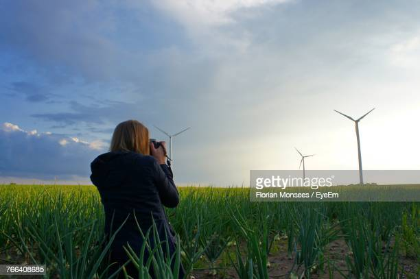 Rear View Of Woman Crouching On Field Against Sky