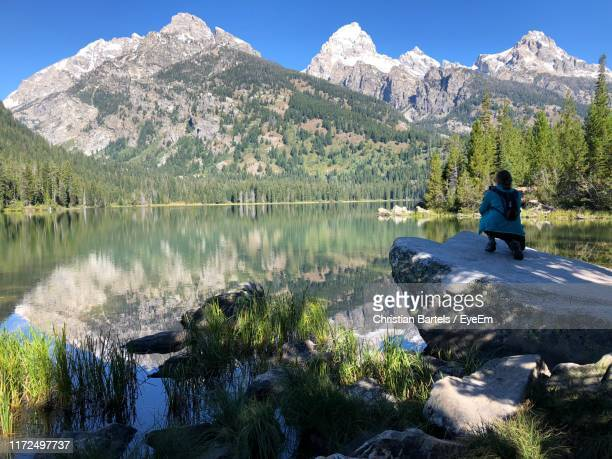 rear view of woman crouching on rock by lake and mountains - beaver creek colorado stock pictures, royalty-free photos & images
