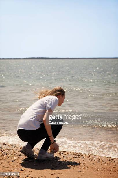 Rear view of woman crouching on shore at beach