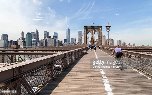 rear view of woman cycling on brooklyn bridge in city against sky - brooklyn bridge stock pictures, royalty-free photos & images