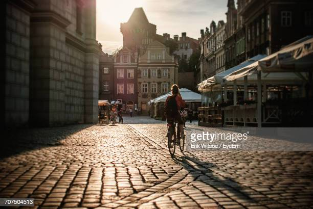 Rear View Of Woman Cycling On Cobbled Street In City During Sunset
