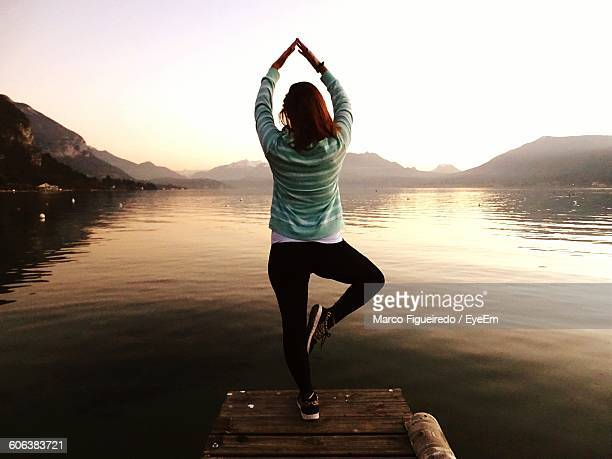 Rear View Of Woman Doing Yoga On Pier Over Lake Against Sky During Sunrise