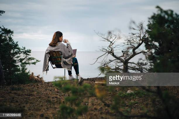 rear view of woman drinking coffee while sitting with laptop on chair against lake - gemak stockfoto's en -beelden