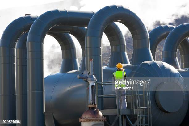 rear view of woman engineer standing on a platform at a geothermal plant. - energia geotermica fotografías e imágenes de stock