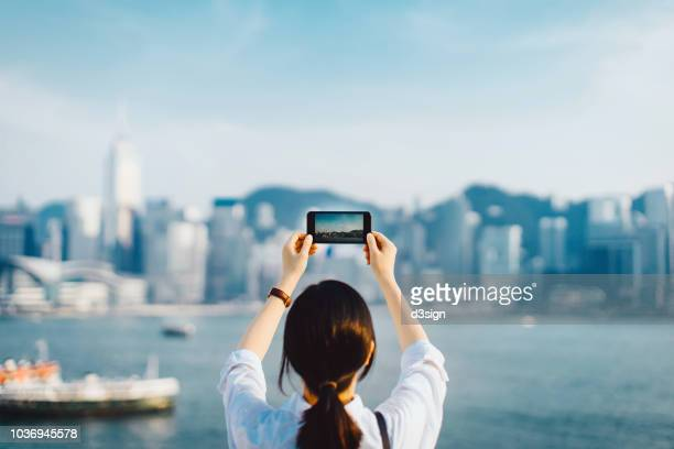 rear view of woman enjoying the spectacular view over victoria harbour and taking picture of hong kong city skyline with smartphone on a sunny day - capturing an image stock pictures, royalty-free photos & images
