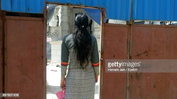 rear view of woman entering gate - salwar kameez stock pictures, royalty-free photos & images