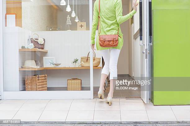 Rear view of woman entering shop