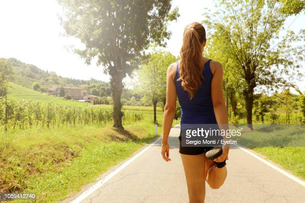 rear view of woman exercising on road - running shorts stock pictures, royalty-free photos & images
