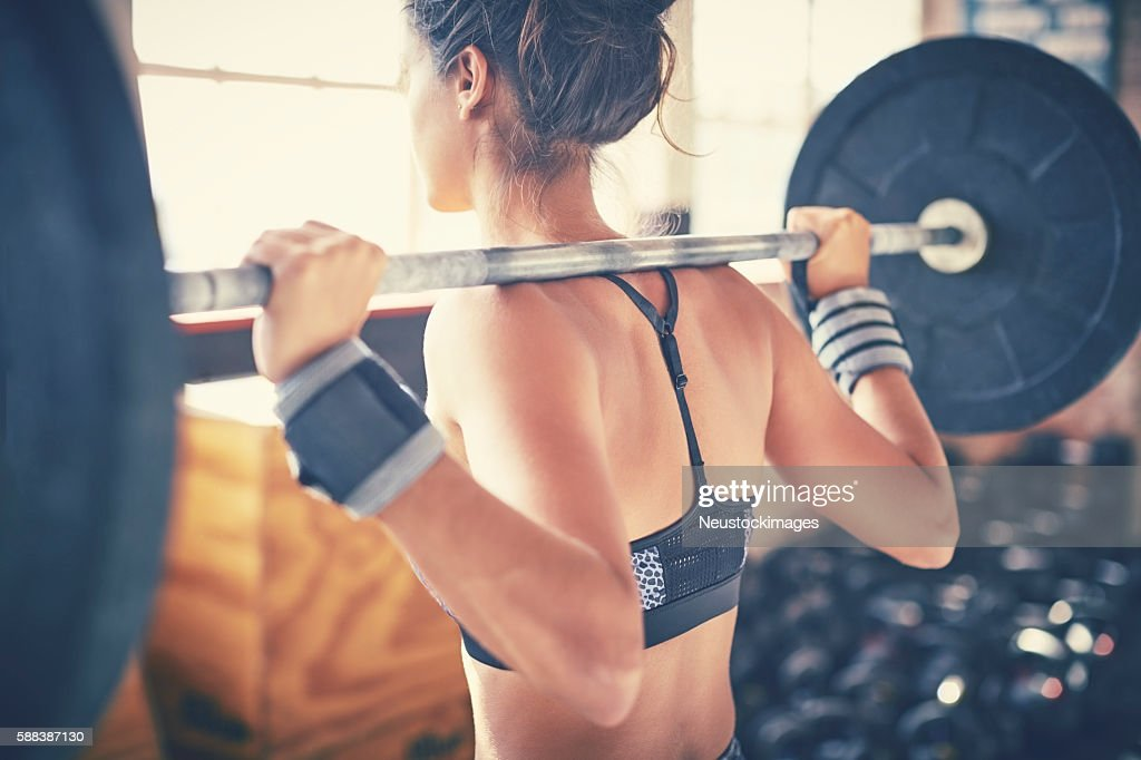 Rear view of woman exercising with barbell in gym : Stock Photo