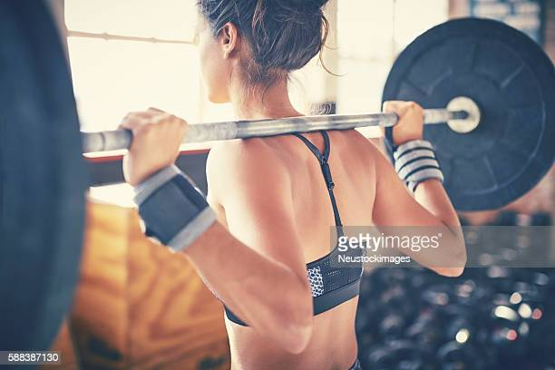 rear view of woman exercising with barbell in gym - bodybuilding stockfoto's en -beelden