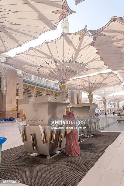 Rear View Of Woman Filling Bottle From Water Cooler At Al-Masjid An-Nabawi