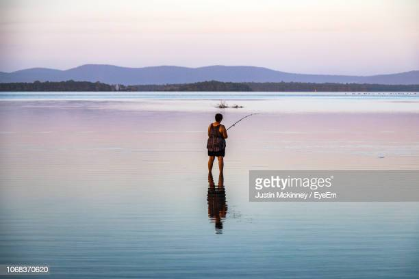Rear View Of Woman Fishing In Lake During Sunset