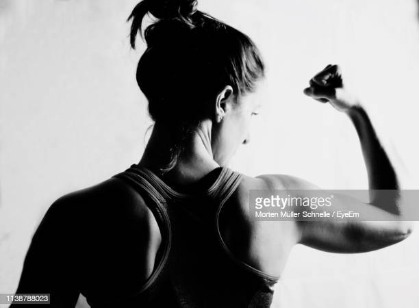 rear view of woman flexing muscle against white background - morten müller schnelle stock-fotos und bilder