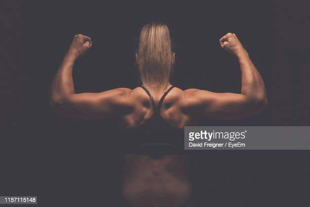 rear view of woman flexing muscles against black background - female bodybuilder stock pictures, royalty-free photos & images