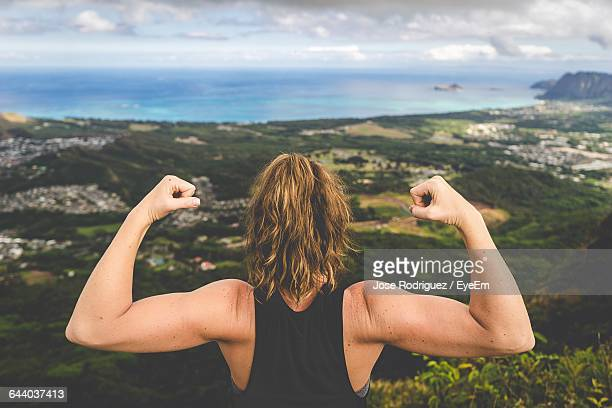 rear view of woman flexing muscles against landscape - flexing muscles stock pictures, royalty-free photos & images