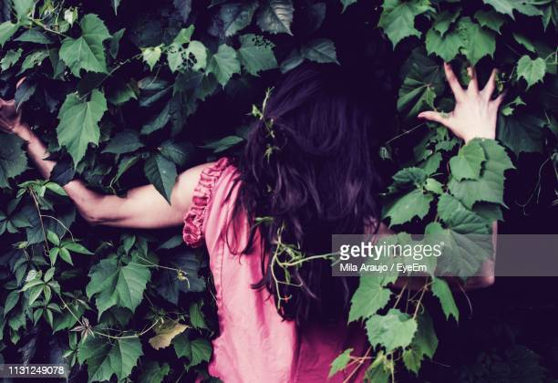 Rear View Of Woman Gesturing Against Plants