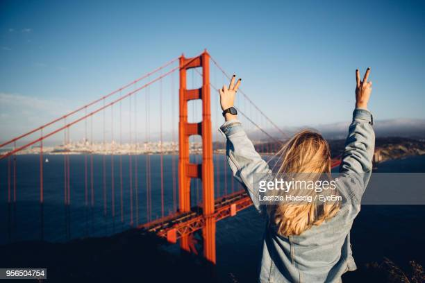 rear view of woman gesturing by suspension bridge against sky - san francisco california stock pictures, royalty-free photos & images