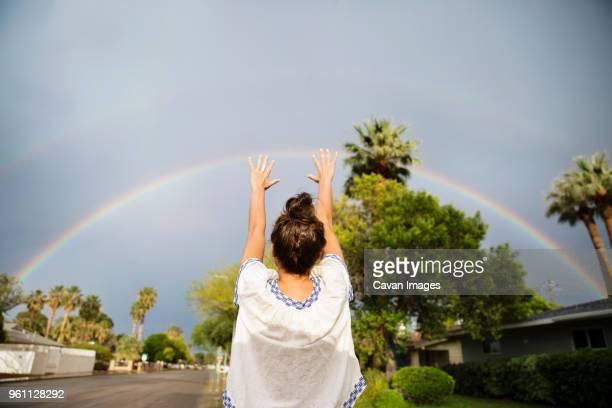 rear view of woman gesturing towards rainbow during rainy season - nur erwachsene stock-fotos und bilder