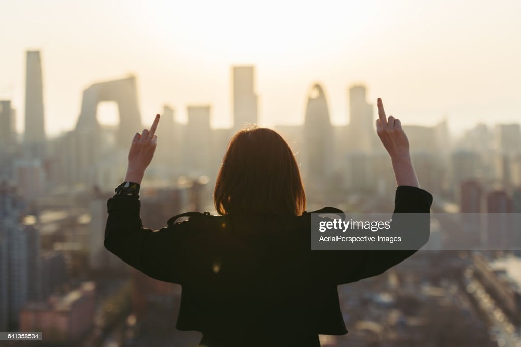 Rear View of Woman Giving Middle Finger in City : Stock Photo