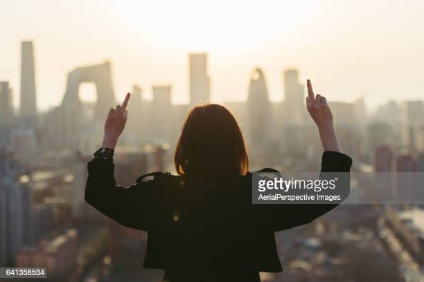 rear view of woman giving middle finger in city - opstand stockfoto's en -beelden