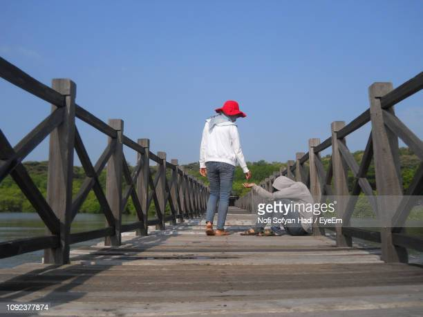 Rear View Of Woman Giving Money To Beggar Sitting On Footbridge Against Clear Sky