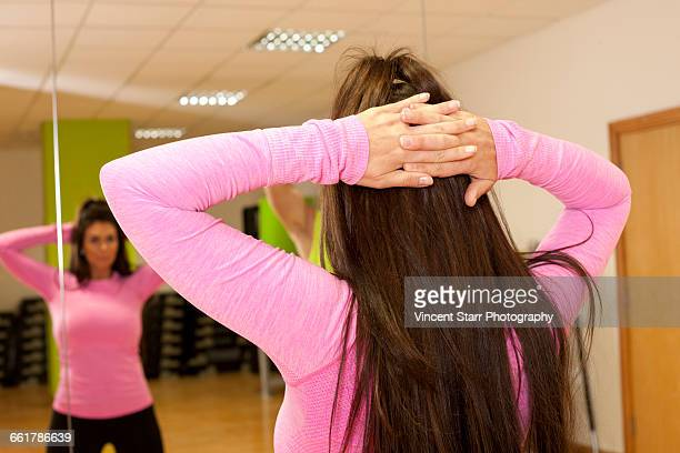 Rear view of woman hands behind head doing stretching exercise