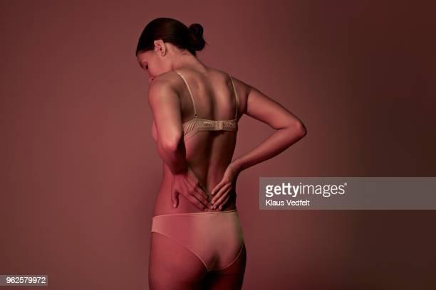 rear view of woman having back pain - hernie stock-fotos und bilder