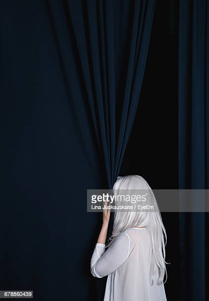 Rear View Of Woman Hiding By Curtain
