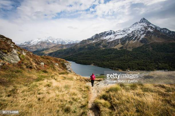 Rear View Of Woman Hiking On Mountain Against Sky