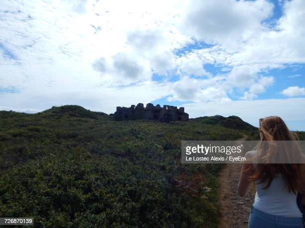 Rear View Of Woman Hiking On Trail Against Sky During Sunny Day