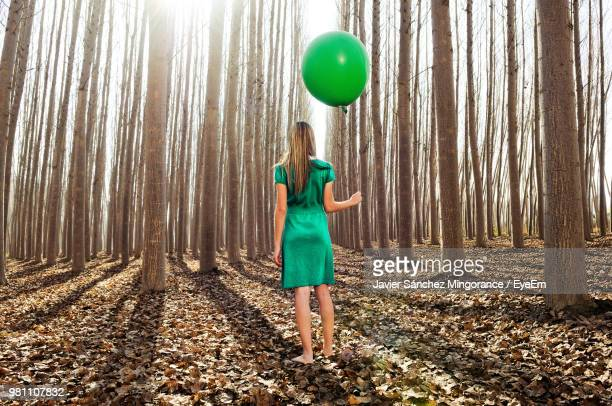 rear view of woman holding balloon while standing in forest - green dress stock pictures, royalty-free photos & images