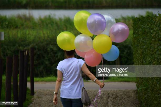 Rear View Of Woman Holding Balloons While Standing At Footpath